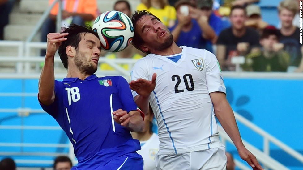 Italy midfielder Marco Parolo, left, and Uruguay midfielder Alvaro Gonzalez vie during a match at the Dunas Arena in Natal.