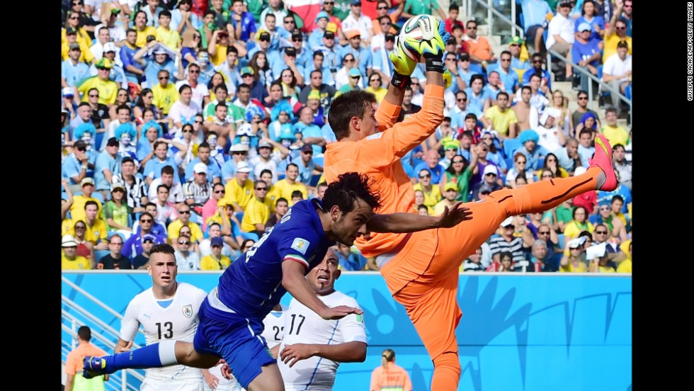 Uruguay goalkeeper Fernando Muslera grabs the ball away from Italy's Marco Parolo.