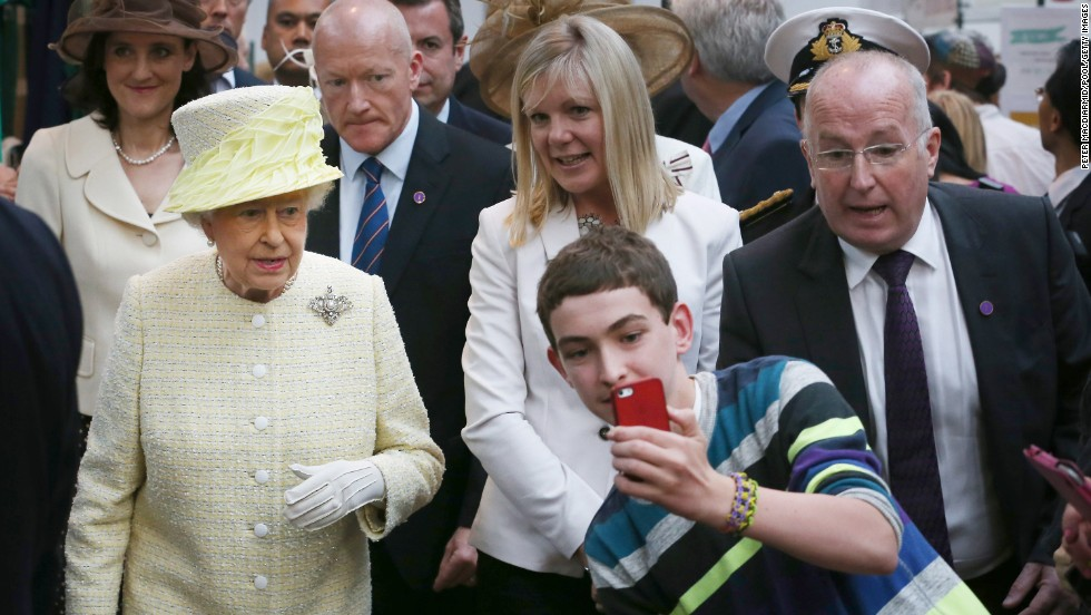 A boy takes a selfie in front of Queen Elizabeth II at St. George's indoor market in Belfast, Northern Ireland, on Tuesday, June 24.