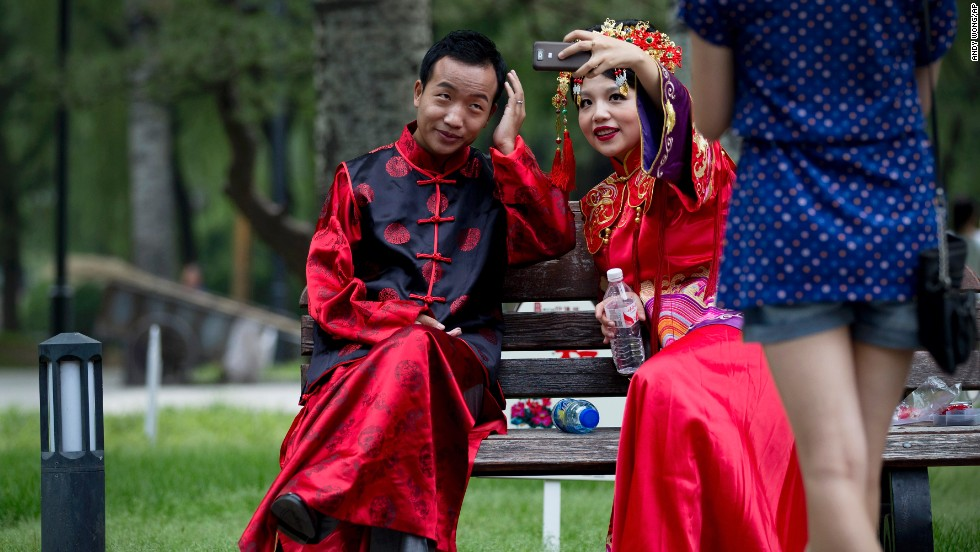 A newly wed Chinese couple take a selfie during a wedding photo shoot at a park in Beijing on Saturday, June 21.