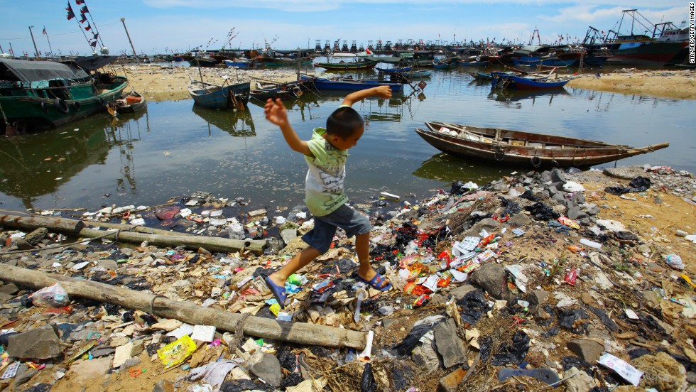 A Chinese boy runs along the trash-strewn beach along the sea coast in Anquan village, which is in Hainan province, in 2011.