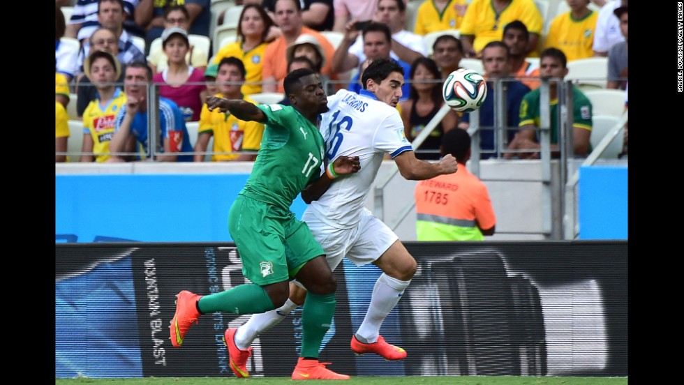 Ivory Coast's Serge Aurier, left, challenges Greece's Lazaros Christodoulopoulos.