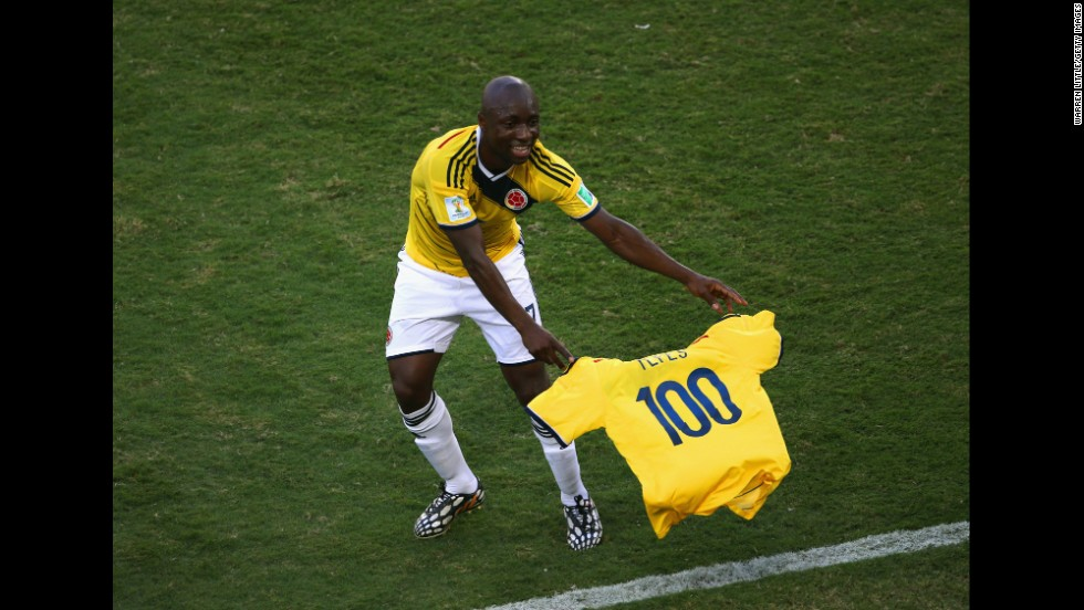 Pablo Armero of Colombia holds up a shirt with the number 100 during the match against Japan.