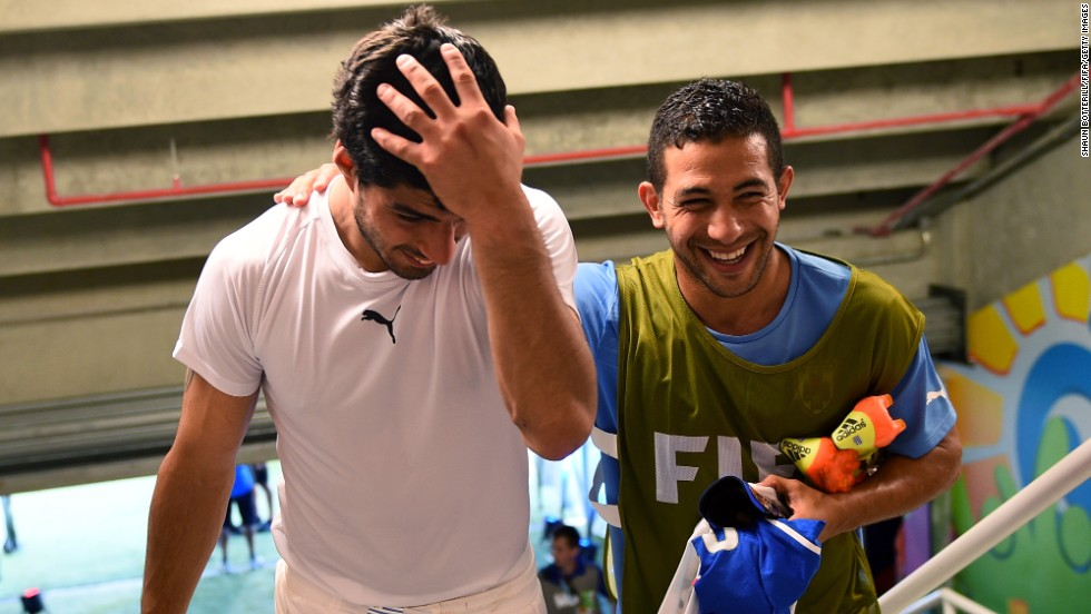 Suarez, left, celebrates the 1-0 win against Italy with his teammate Walter Gargano in the tunnel after the controversial match at Estadio das Dunas.