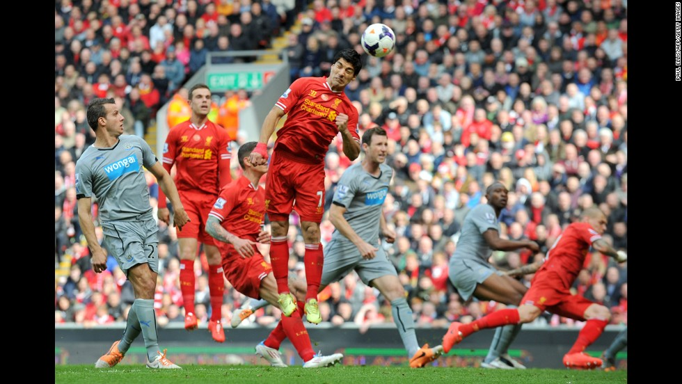 Suarez, fourth from left, heads the ball for teammate Daniel Sturridge to score his team's second goal during the English Premier League football match between Liverpool and Newcastle United on May 11.