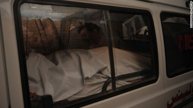 The dead body of a passenger killed in a Peshawar airport shooting is placed in an ambulance.