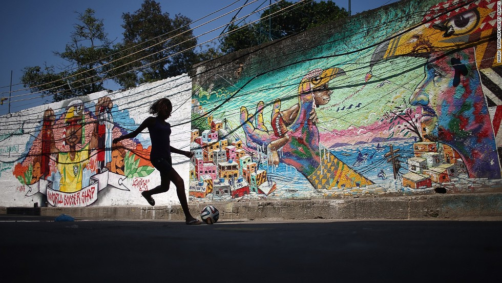 "A girl kicks a football in front of graffiti created by acclaimed artist Acme in the pacified Pavao-Pavaozinho community in Rio de Janeiro, Brazil. <br /><br />Another issue at the heart the protests has been the occupation and ""pacification"" of some of the poorest slums in Brazil by the police and military in an attempt to reduce crime during the tournament."