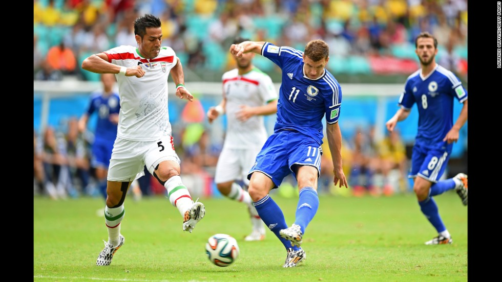 Edin Dzeko of Bosnia-Herzegovina shoots and scores his team's first goal.