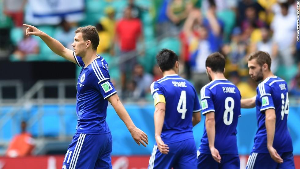 Bosnia-Herzegovina forward Edin Dzeko, left, celebrates scoring his team's first goal against Iran.