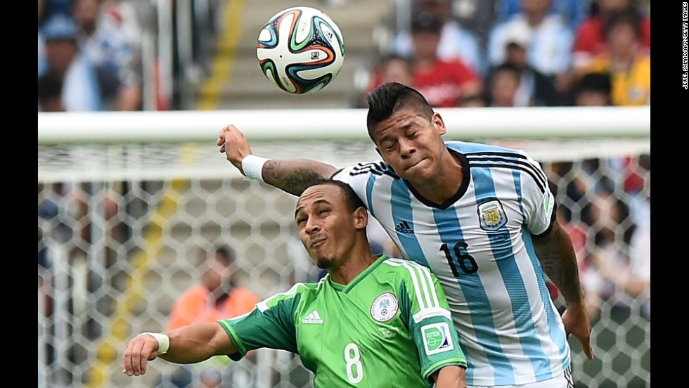 Argentina defender Marcos Rojo, right, challenges Nigeria forward Peter Odemwingie for the ball.