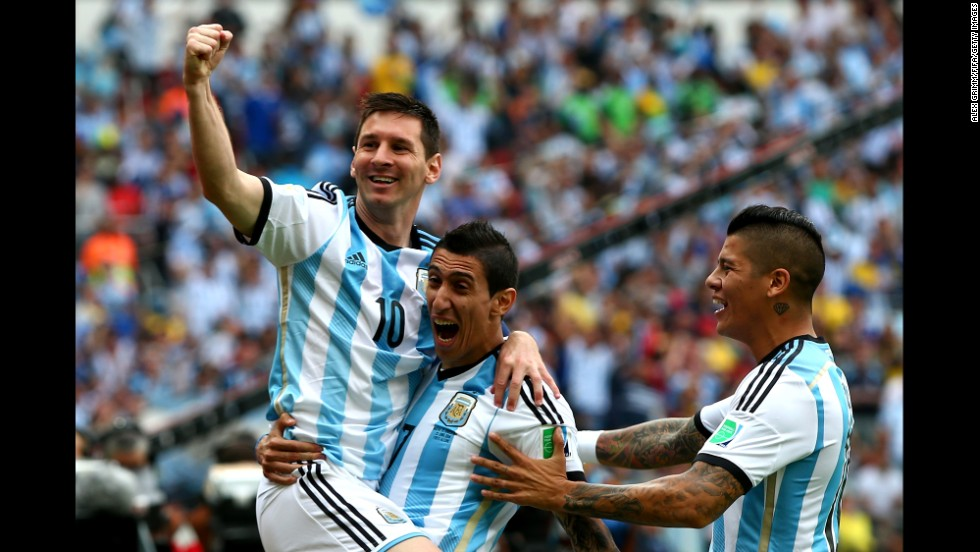 Lionel Messi, left, of Argentina celebrates scoring his team's first goal with his teammates Angel di Maria, center, and Marcos Rojo, right, during the match between Nigeria and Argentina.