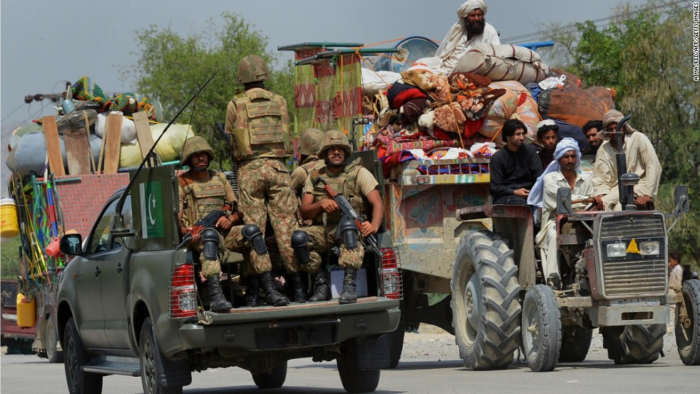 Pakistani troops patrol as displaced civilians cross a checkpoint.