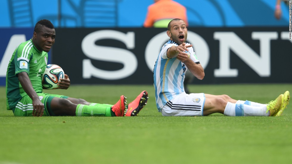 Nigeria's forward Emmanuel Emenike and Argentina's midfielder Javier Mascherano gestures from the field.