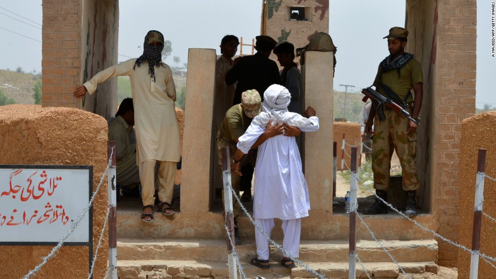 A Pakistani soldier frisks a civilian at the Bannu Frontier Region registration point for displaced people on June 22. At registration centers, people are receiving cash handouts to buy food and other items, the U.N. says.