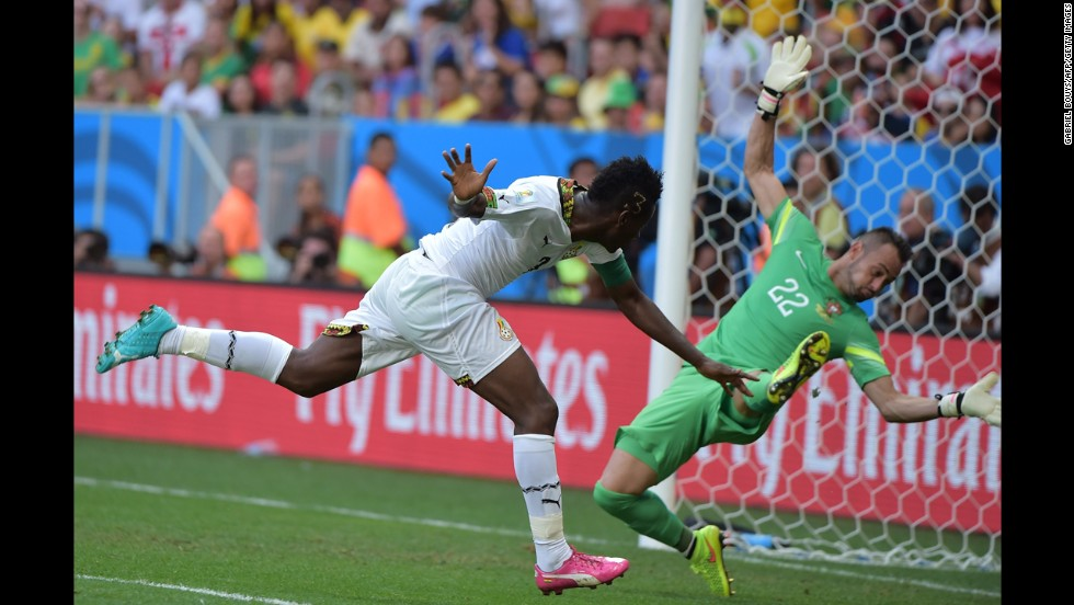 Ghana forward and captain Asamoah Gyan, left, scores past Portugal's goalkeeper Beto during the match between Portugal and Ghana.