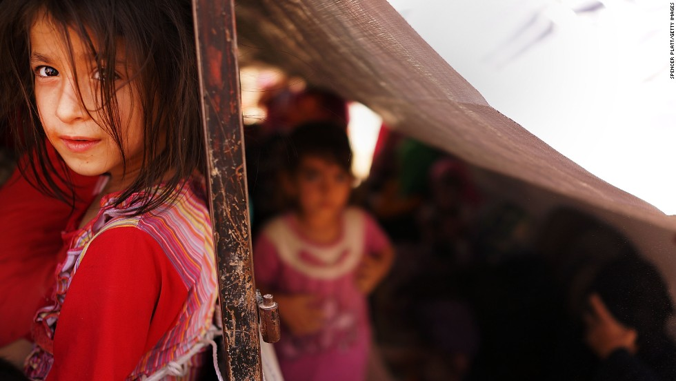"JUNE 26 - KHAZAIR, IRAQ: A young girl waits with her family to get into a temporary displacement camp for Iraqis fleeing the violence in the city of Mosul.<a href=""http://cnn.com/2014/06/26/world/meast/iraq-crisis/index.html""> As Sunni extremist militants and the Iraqi military battle for control,</a> the nation's Vice President has called for the formation of a new government to tackle the crisis."