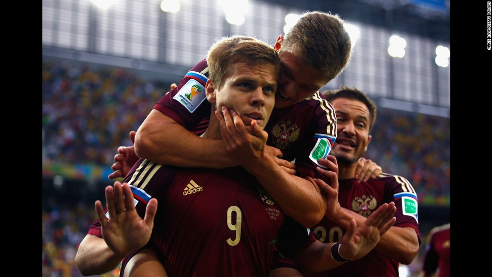 Kokorin celebrates scoring his team's first goal with teammate Oleg Shatov on his back in a match against Algeria.