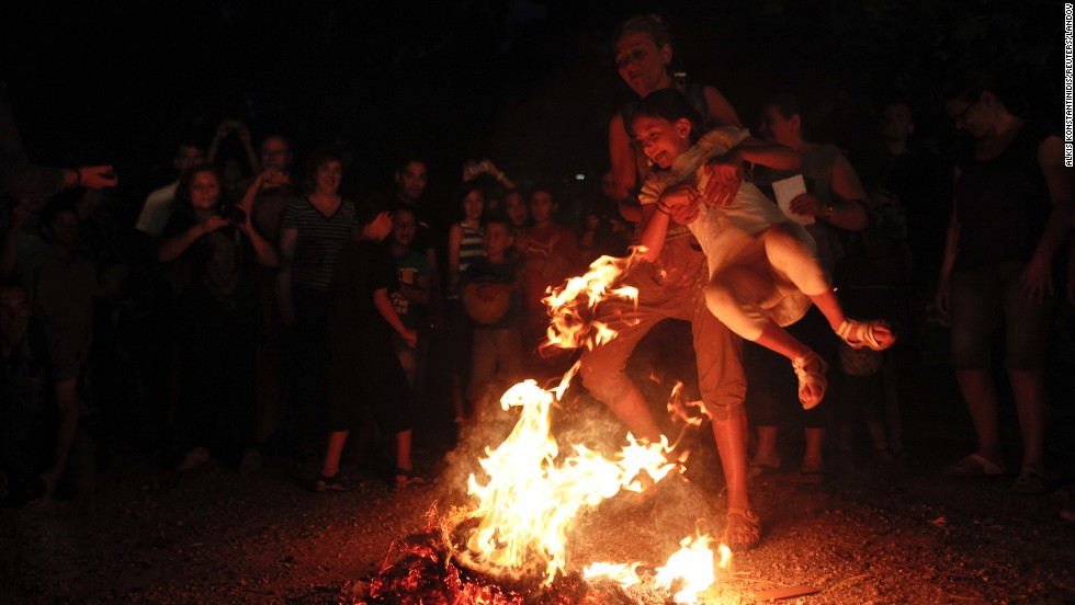 A woman helps a girl cross a fire as part of a traditional custom on Saint John's Eve in Athens, Greece, on Monday, June 23.