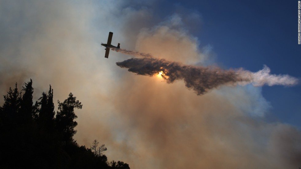 An airplane drops water over a forest in an attempt to control wildfires near the Jerusalem neighborhood of Ein Kerem on Wednesday, June 25.
