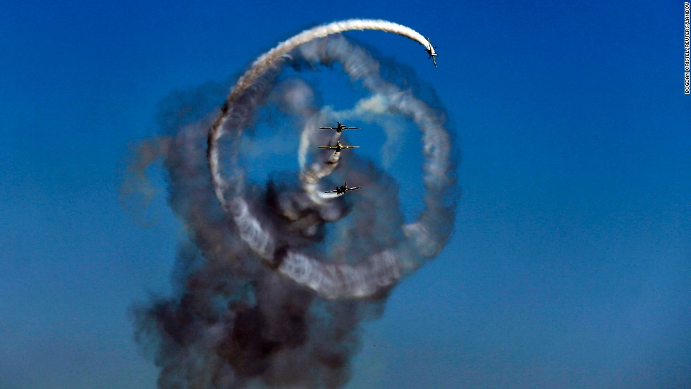 The Aerobatic Yakkers team performs on YAK-52 airplanes during the Bucharest International Air Show in the Romanian capital.