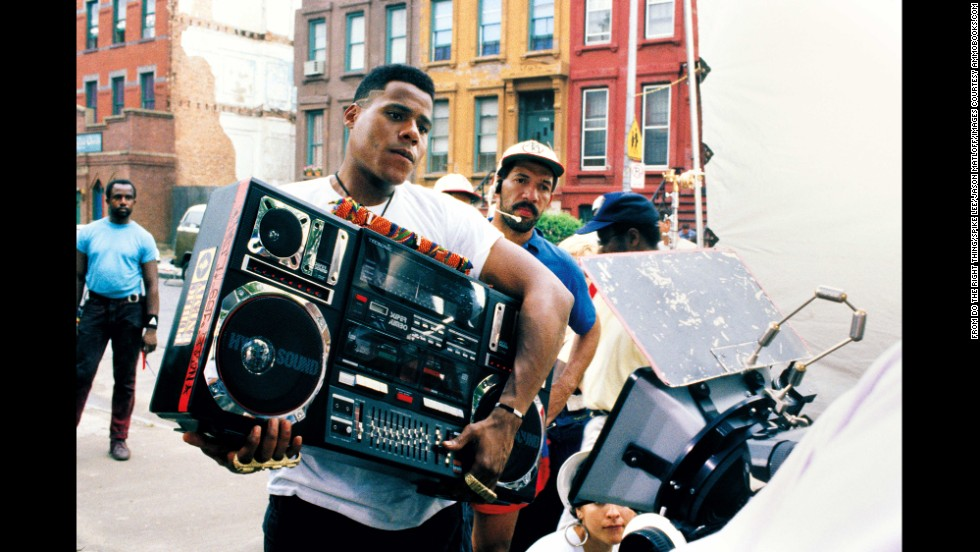 "The film is set on a hot day in Brooklyn, New York, and follows the lives of several characters. One of them, Radio Raheem (Bill Nunn), likes to walk around the neighborhood playing Public Enemy's ""Fight the Power"" at high volume, annoying some and entertaining others."