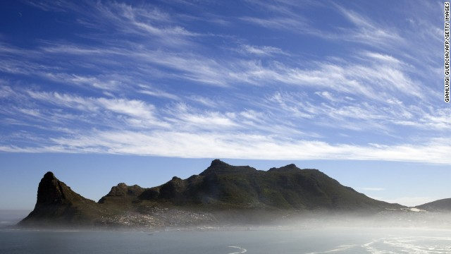 A general view of the Hout Bay harbour covered in mist is seen on May 8, 2010 from the Chapman's peak road on the outskirts of Cape Town. Chapman's peak road is the coastal link between Cape Town and the Cape of Good Hope. When following the African coastline from the equator the Cape of Good Hope marks the psychologically important point where one begins to travel more eastward than southward, thus the first rounding of the cape in 1488 by Portuguese explorer Bartolomeu Dias was a major milestone in the attempts by the Portuguese to establish direct trade relations with the Far East. He called the cape Cabo Tormentoso. As one of the great capes of the South Atlantic Ocean, the Cape of Good Hope has been of special significance to sailors for many years and is widely referred to by them simply as 'the Cape'. It is a major milestone on the clipper route followed by clipper ships to the Far East and Australia, and still followed by several offshore yacht races. AFP PHOTO/GIANLUIGI GUERCIA (Photo credit should read GIANLUIGI GUERCIA/AFP/Getty Images)