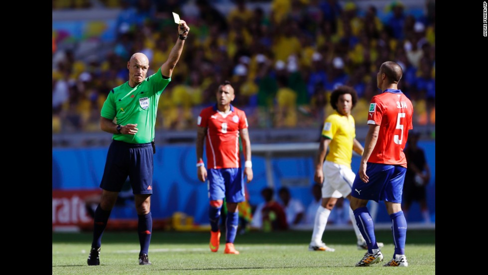 Referee Howard Webb gives a yellow card to Chile's Francisco Silva.