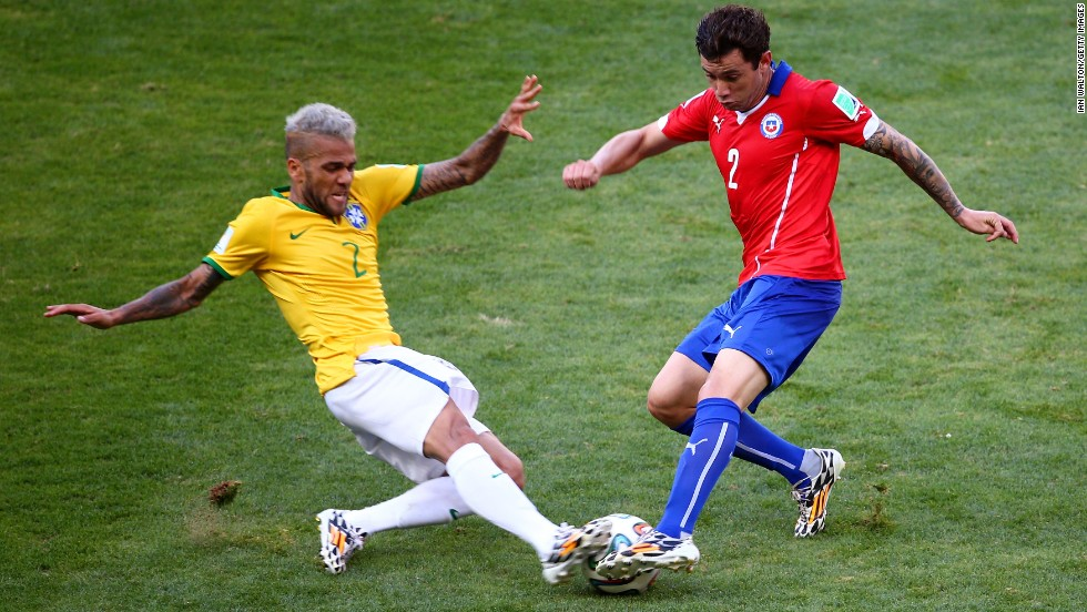 Dani Alves of Brazil and Eugenio Mena of Chile compete for the ball before the game went into penalty shootout.