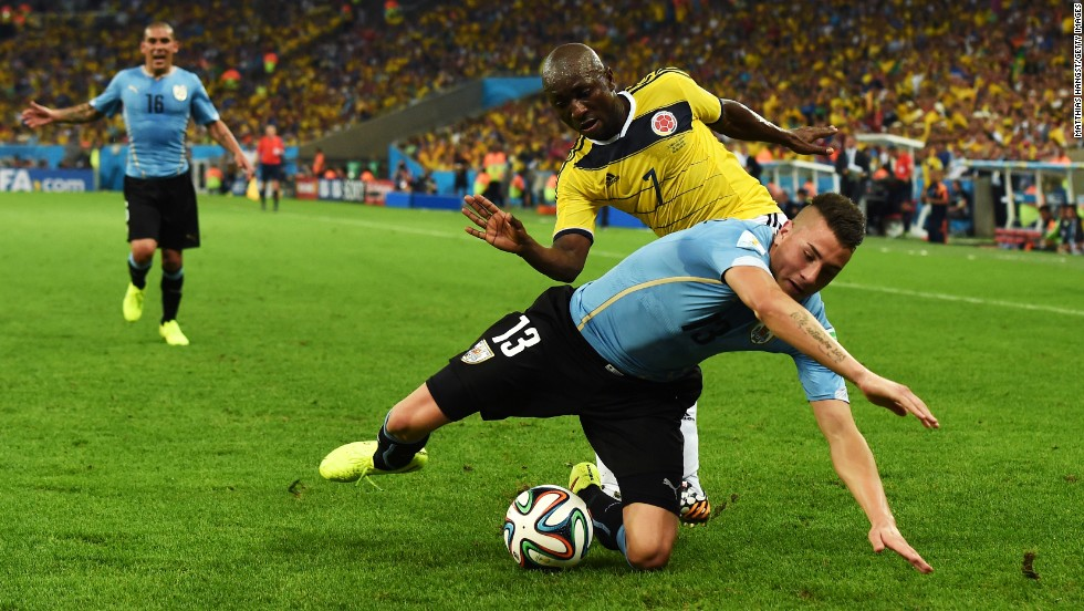 Jose Gimenez, in blue, of Uruguay is challenged by Pablo Armero of Colombia.