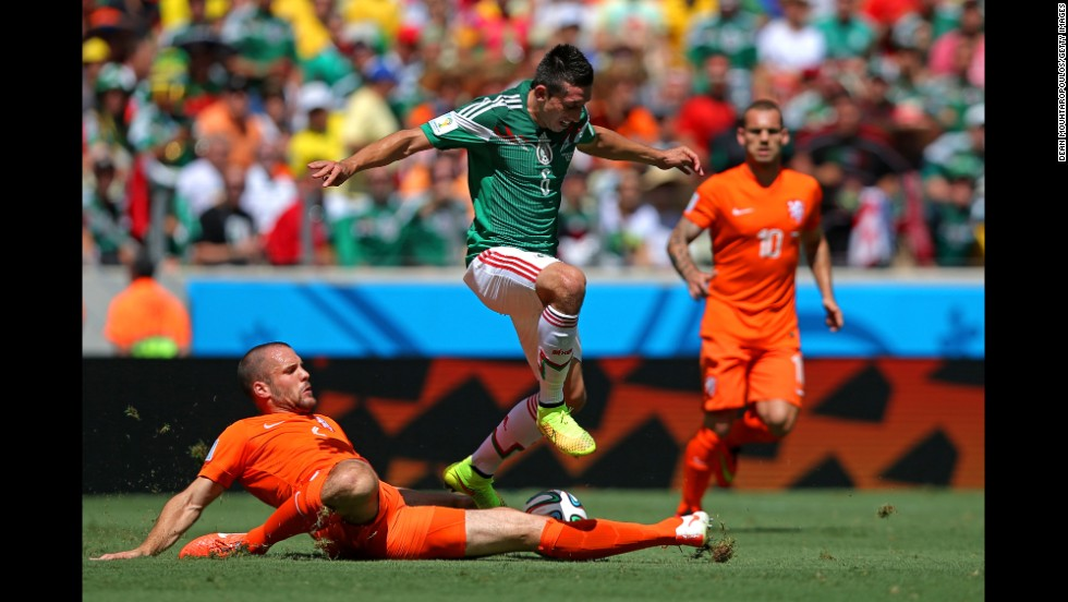 Ron Vlaar of the Netherlands tackles Hector Herrera of Mexico.