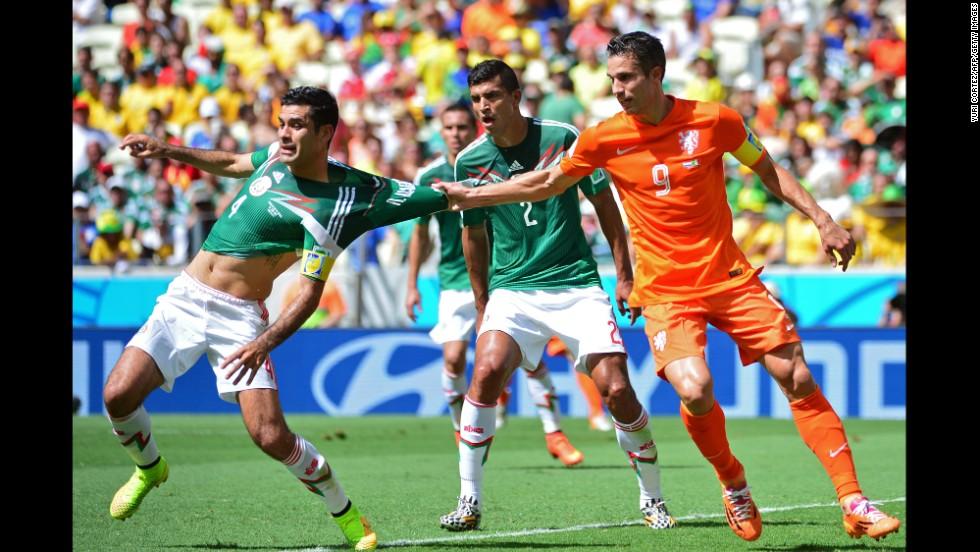 Netherlands forward Robin van Persie pulls the jersey of Mexico's captain Rafael Marquez.