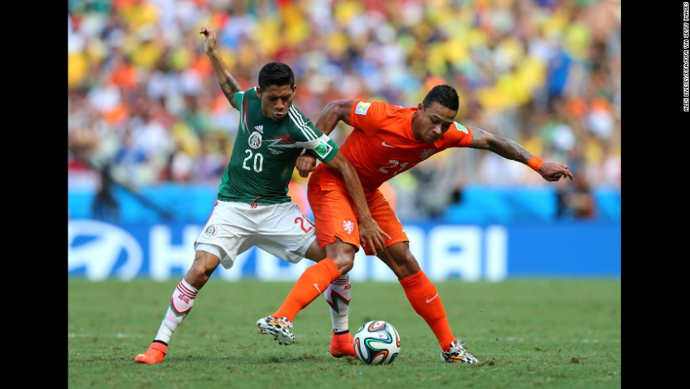 Memphis Depay of the Netherlands and Javier Aquino of Mexico compete for the ball.