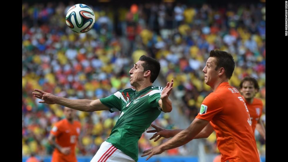 Mexico's Hector Herrera vies for the ball with Netherlands' Stefan de Vrij.