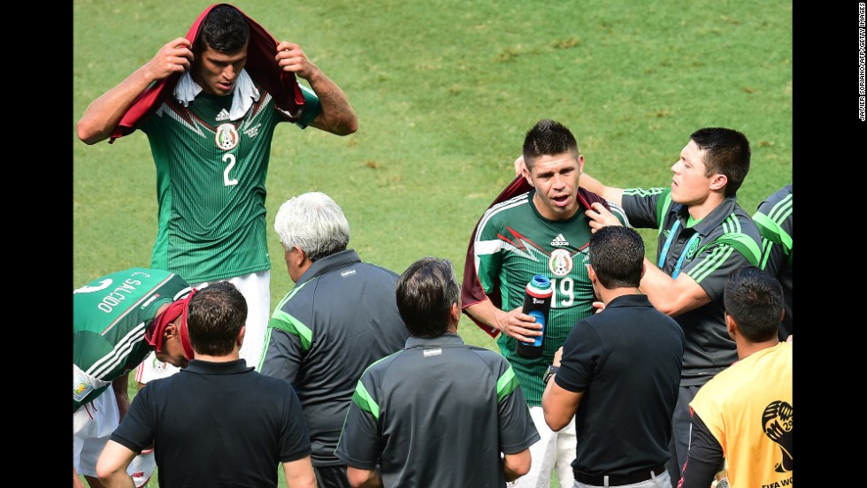 Francisco Rodriguez, left, and Oribe Peralta, second right, of Mexico take a three-minute cooling break allowed for both teams by the referee during the 30th and 75th minutes of the game.