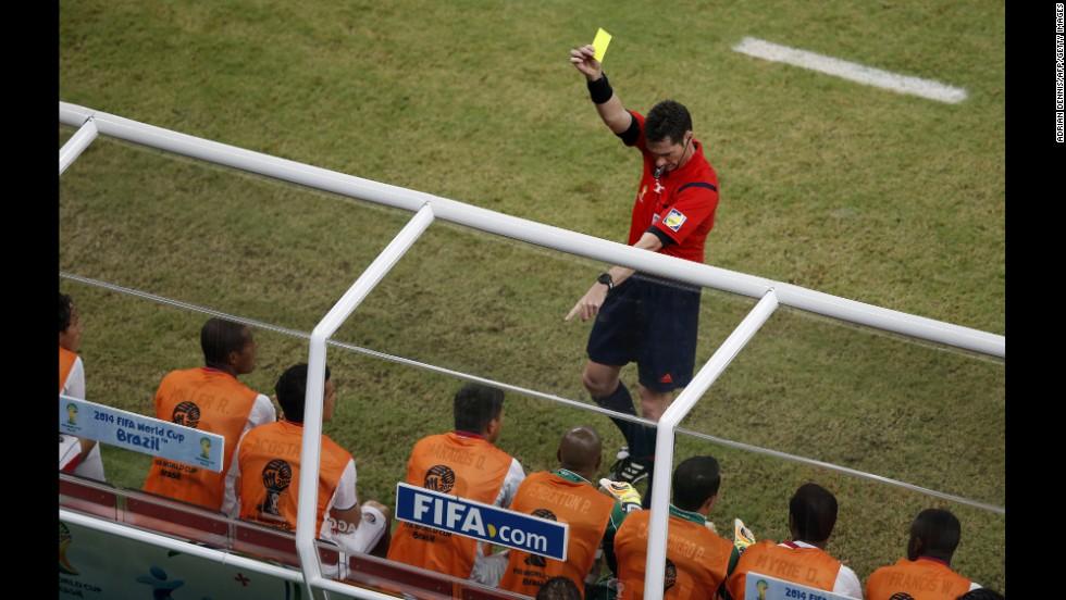 Referee Benjamin Williams gives a yellow card to Costa Rica's Oscar Esteban Granados on the sideline.