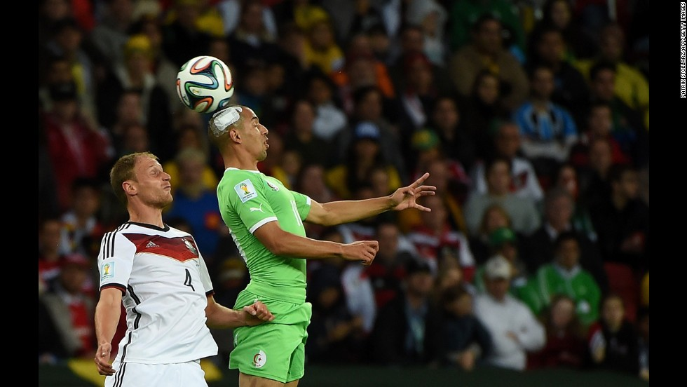 German defender Benedikt Hoewedes, left, competes for the ball with Algeria's Sofiane Feghouli.
