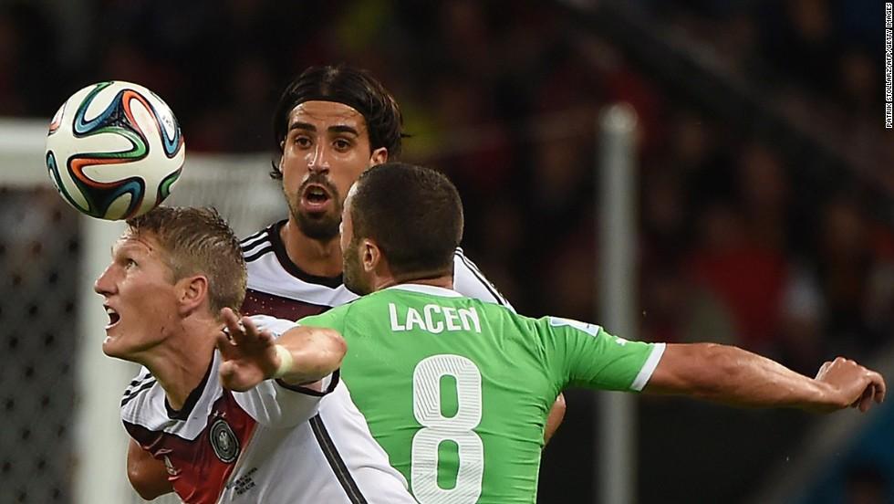 Germany's Bastian Schweinsteiger, left, and Sami Khedira fight for the ball with Algeria midfielder Medhi Lacen.