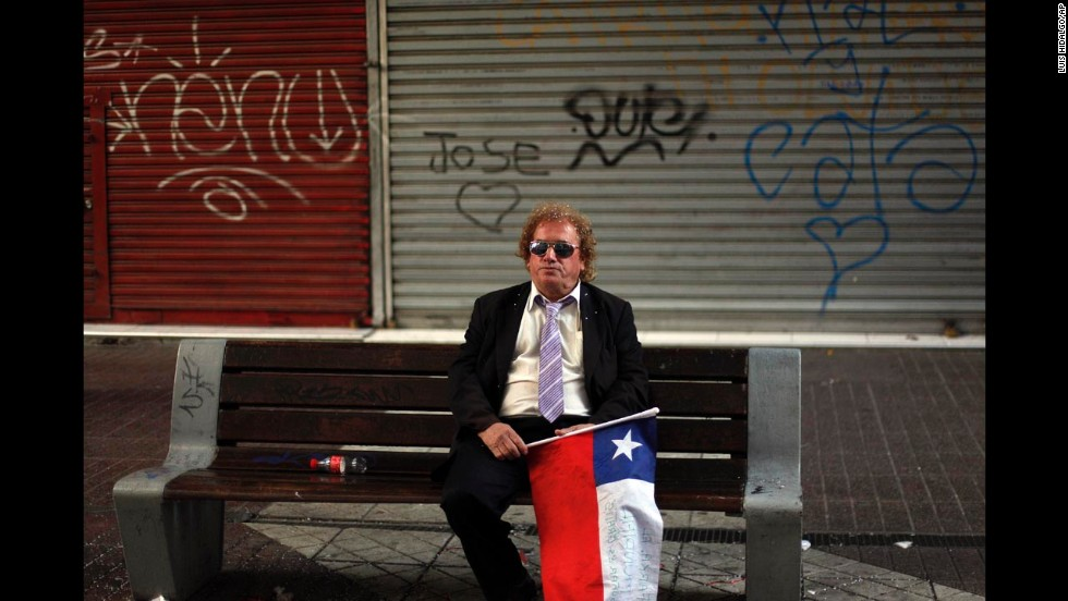 A man holding a Chilean flag sits alone on a street bench in Santiago, Chile, after Chile was defeated by Brazil and knocked out of the World Cup on Saturday, June 28.
