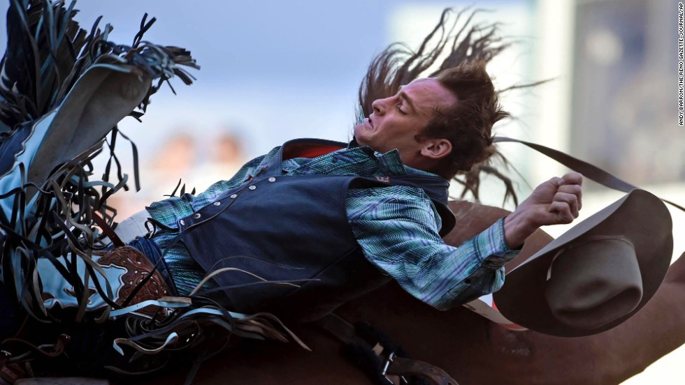 Kyle Brennecke loses his hat Wednesday, June 25, as he competes in bareback bronc riding at the Reno Rodeo in Reno, Nevada.