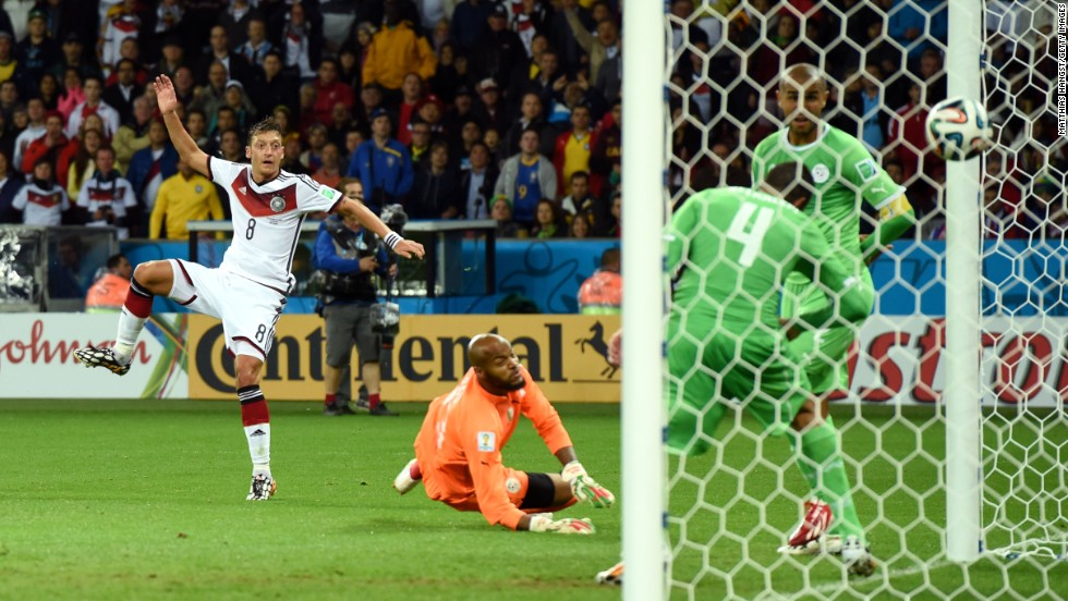 Mesut Oezil of Germany scores his team's second goal past Rais M'Bolhi of Algeria.