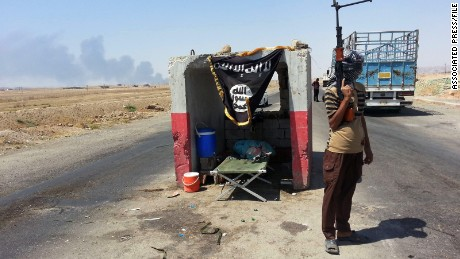 An ISIS militant stands guard at a checkpoint captured from the Iraqi Army outside Beiji refinery, 155 miles north of Baghdad, on June 19.