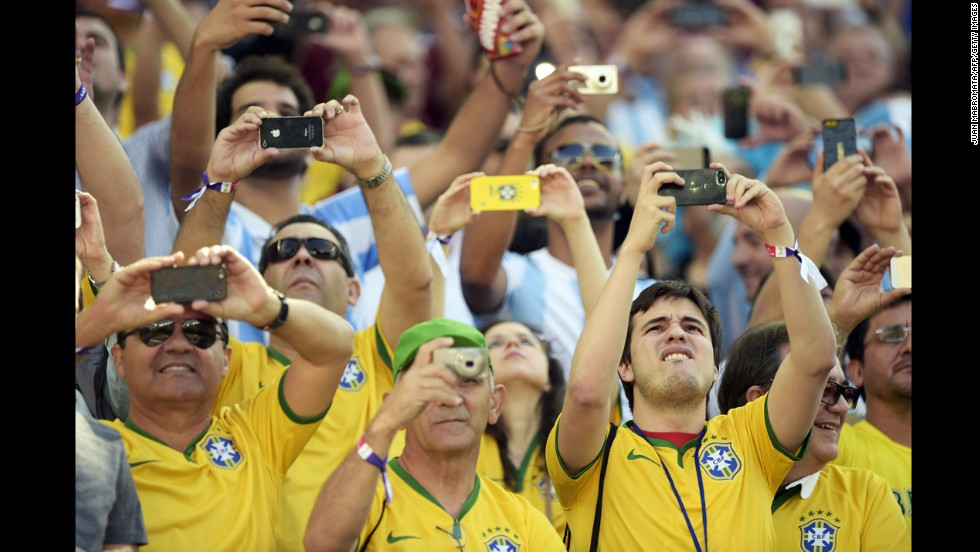 Fans wearing Brazil jerseys take pictures prior to the start of the match.