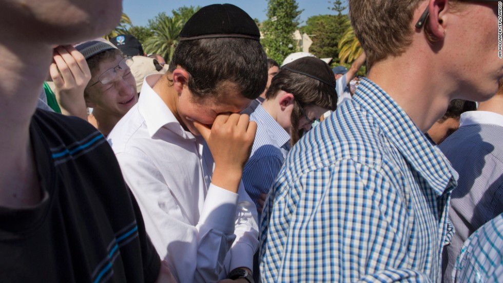 Friends of Naftali Frankel attend his funeral service.