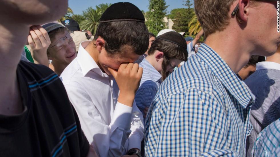 Friends of Naftali Frankel attend his funeral service.