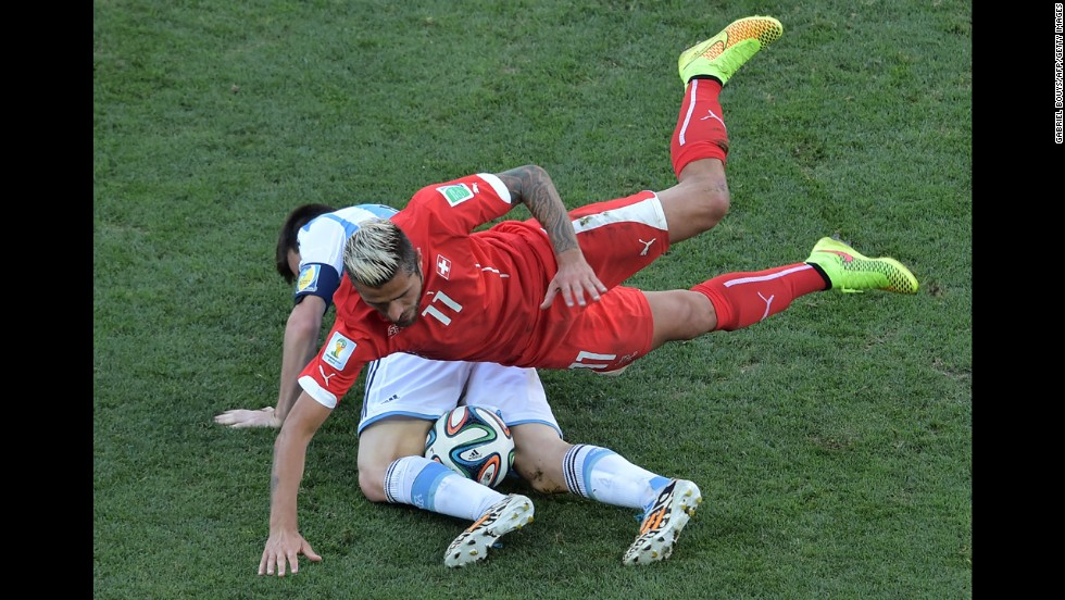Swiss midfielder Valon Behrami falls on Messi.
