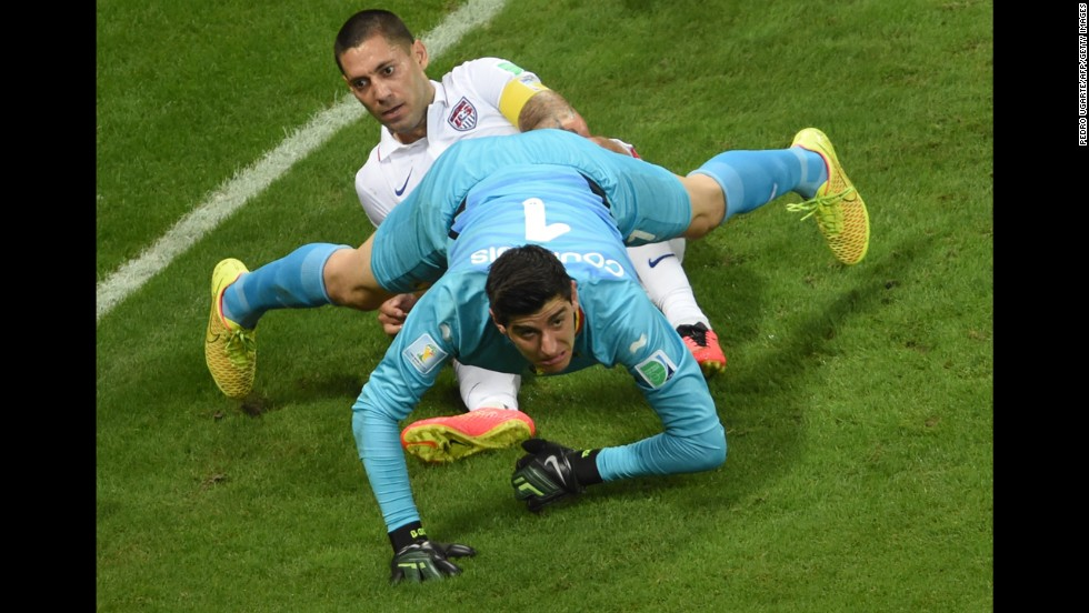 Belgium's goalkeeper, Thibaut Courtois, falls on U.S. forward Clint Dempsey.