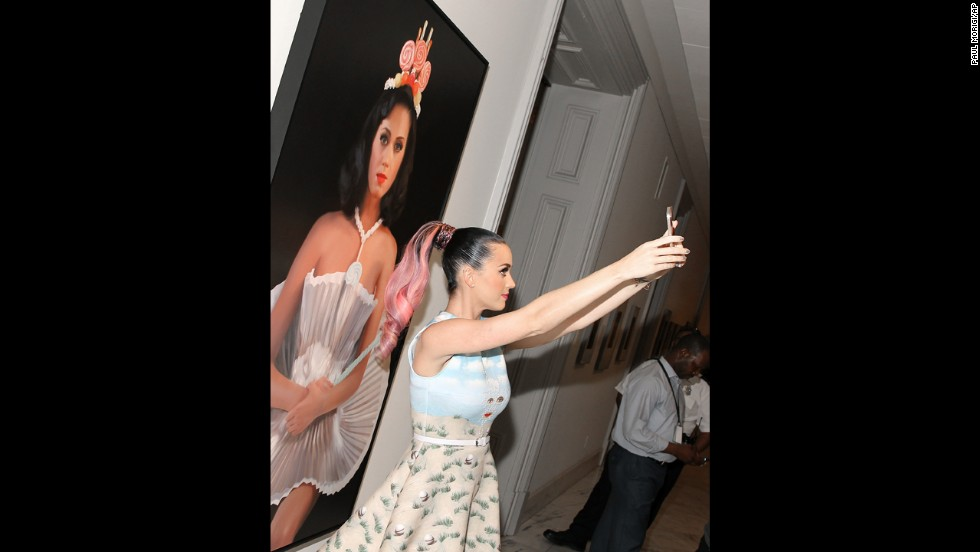 "Pop star Katy Perry takes a selfie with a painting of herself Wednesday, June 25, at the Smithsonian's National Portrait Gallery in Washington. The painting, by artist Will Cotton, is called ""Cupcake Katy."""