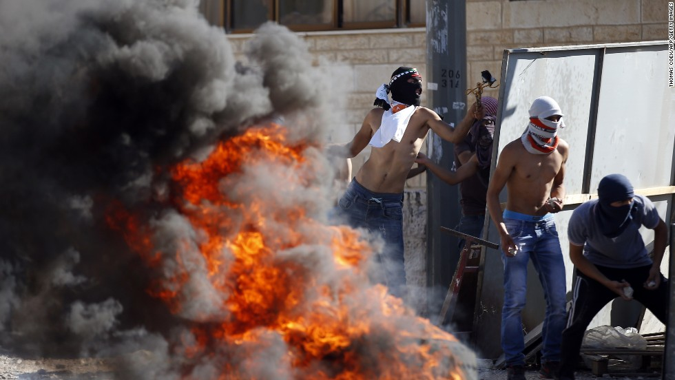 Masked Palestinian protesters throw stones towards Israeli police (unseen) during clashes in the Shuafat neighborhood in Jerusalem, on July 2, 2014.