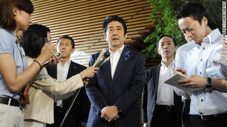 Japanese Prime Minister Shinzo Abe (C) speaks to reporters at his official residence in Tokyo on July 3, 2014. Japan will revoke some of its unilateral sanctions on North Korea, the prime minister announced on July 3, after talks on the Cold War kidnapping of Japanese nationals. Abe said Tokyo judged Pyongyang, which pledged to re-investigate the disappearance of missing Japanese citizens, had shown sufficient willing in resolving the decades-old row and that this needed to be reciprocated. JAPAN OUT AFP PHOTO / JIJI PRESS (Photo credit should read JIJI PRESS/AFP/Getty Images)