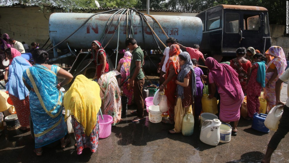 Residents fill up their baskets with water from a tanker April 24 in New Delhi.